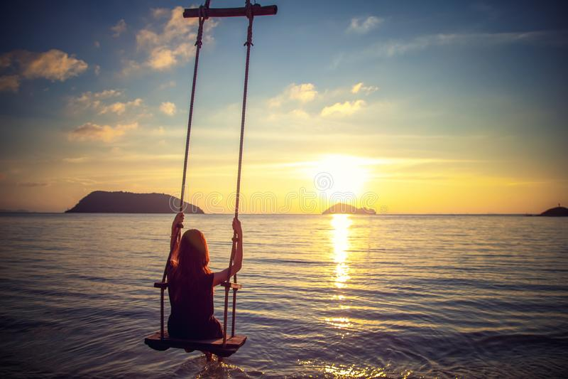 摇摆在海滩的摇摆的年轻美丽的愉快的妇女在日落,放松的旅行生活方式概念期间 免版税图库摄影