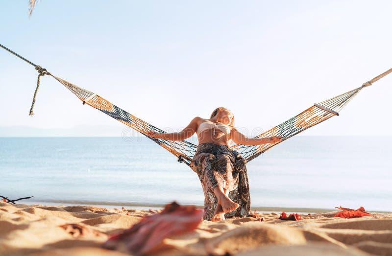 摇摆在温文地弯曲她的身体的含沙海洋海滩的吊床的妇女享受日出光 免版税库存照片