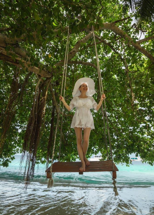 摇摆在热带海滩的白色礼服的妇女 库存图片