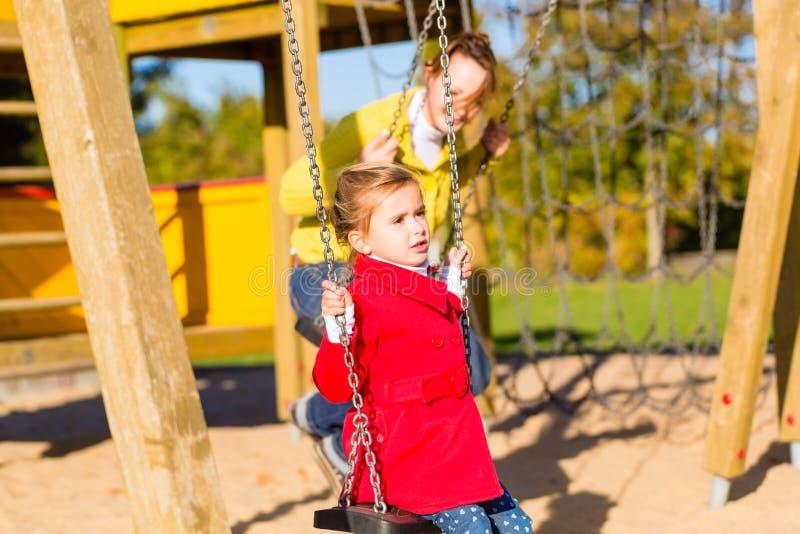 摇摆在玩耍区域或法院的女孩 免版税库存图片