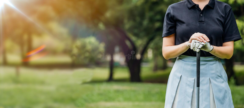 摇摆在绿色领域的年轻女性高尔夫球运动员佩带的运动服接近的画象  年轻女人微笑的高尔夫球运动员和 免版税库存图片