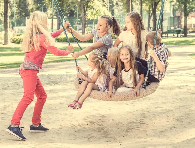 摇摆小孩的白肤金发的女孩 免版税库存照片