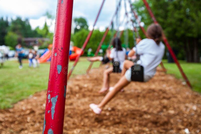 摇摆持有人杆的特写镜头图片 swigning在背景中的孩子 免版税库存照片