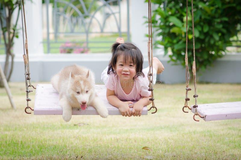 摇摆的亚裔婴孩婴孩与小狗 库存照片