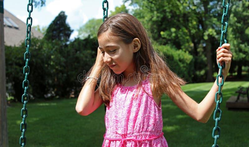 摇摆的可爱的小女孩在有桃红色礼服的公园在夏天期间在密执安 库存照片