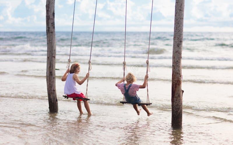 摇摆的孩子 摇摆在海滩的孩子 库存照片