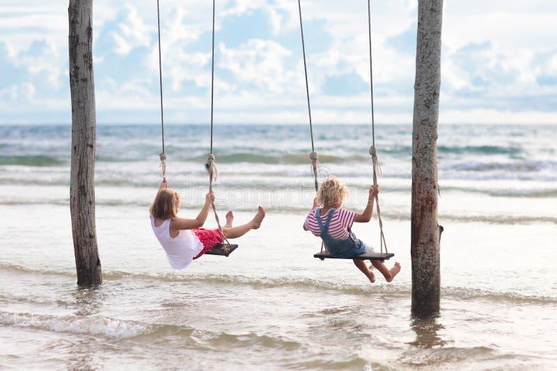 摇摆的孩子 摇摆在海滩的孩子 免版税库存图片
