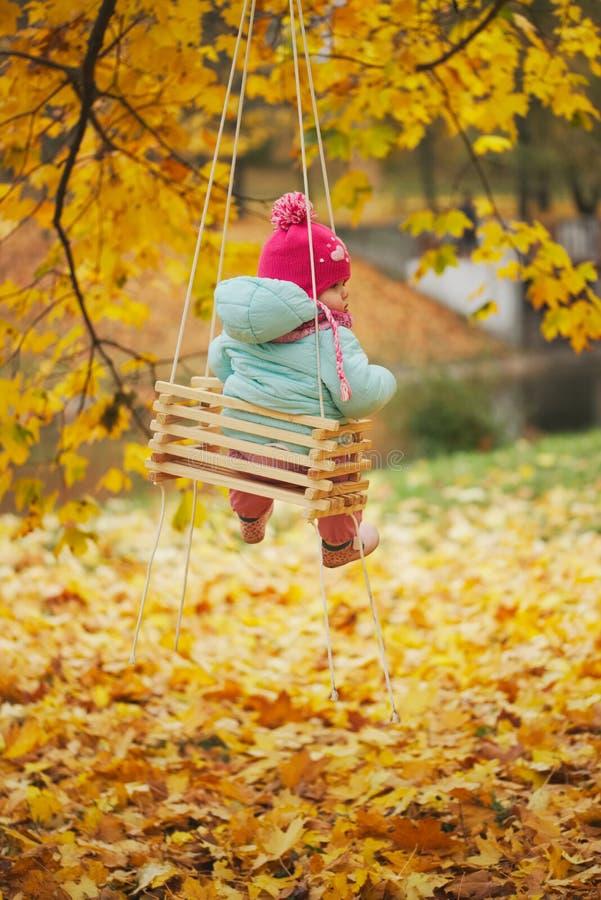 摇摆的小女孩在秋天公园 图库摄影
