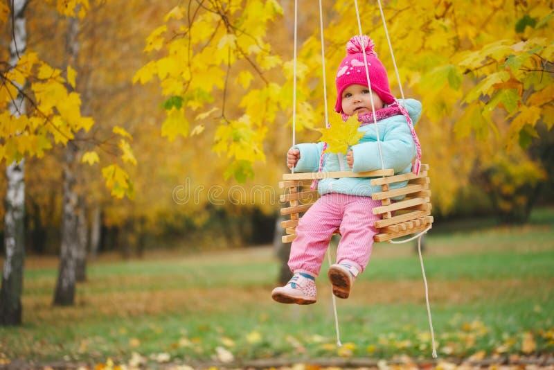 摇摆的小女孩在秋天公园 库存照片