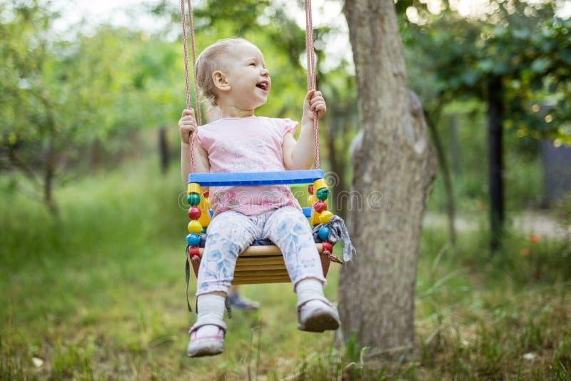摇摆的愉快的女孩在夏天庭院里 库存照片