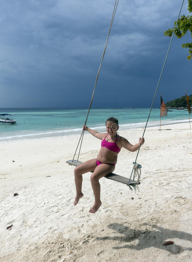 摇摆的愉快的小女孩在海滩 免版税库存照片