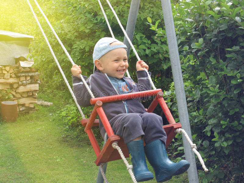 摇摆的愉快的小男孩 免版税图库摄影