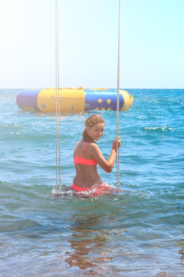 摇摆的愉快的微笑的俏丽的年轻少年女孩在海 库存图片