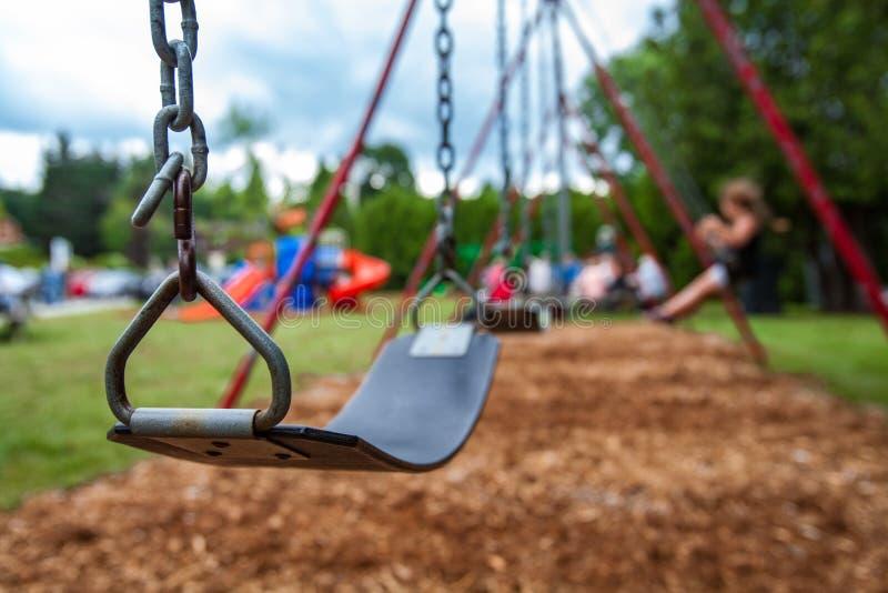 摇摆的特写镜头图片在孩子的一个公园 swigning在背景中的孩子 免版税库存照片