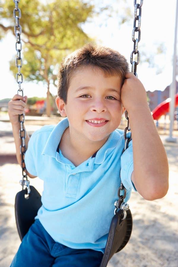 摇摆的男孩在公园 免版税图库摄影
