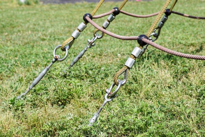 摇摆的绳索吊的结尾在金属建筑的在公园 在金属圈子和安全短冷期勾子的概略的绳索末端 库存照片