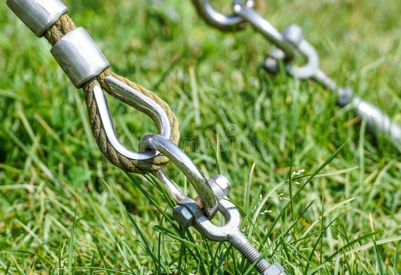 摇摆的绳索吊的结尾在金属建筑的在公园 在金属圈子和安全短冷期勾子的概略的绳索末端 免版税图库摄影