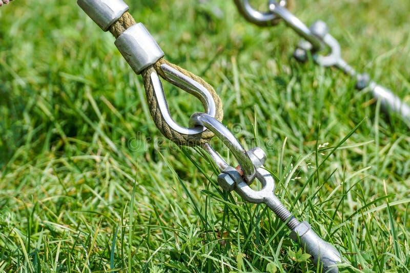摇摆的绳索吊的结尾在金属建筑的在公园 在金属圈子和安全短冷期勾子的概略的绳索末端 图库摄影