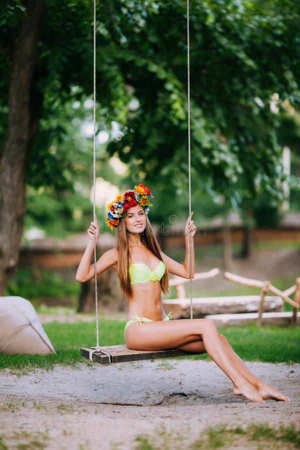 摇摆的美丽的女孩在户外夏日 免版税库存照片
