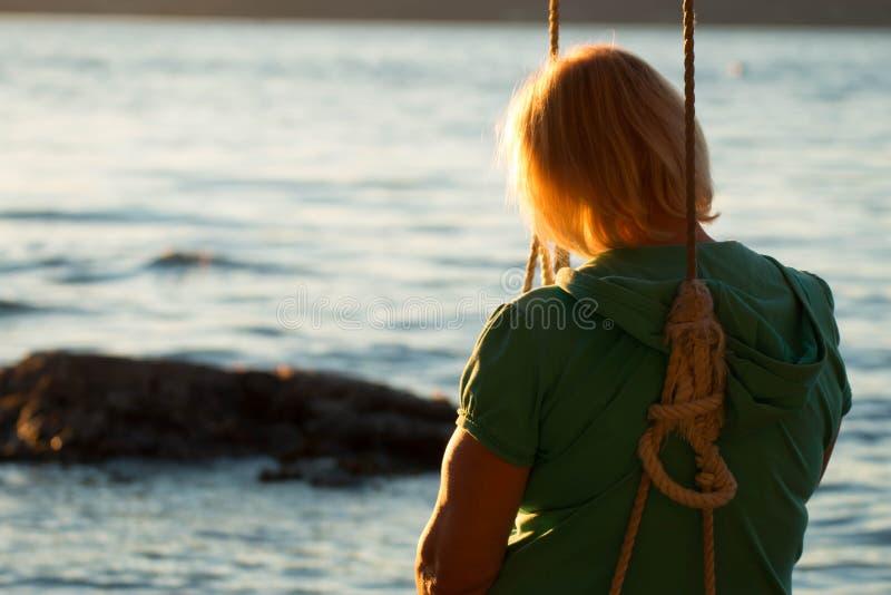 摇摆的资深妇女在海滩 库存照片
