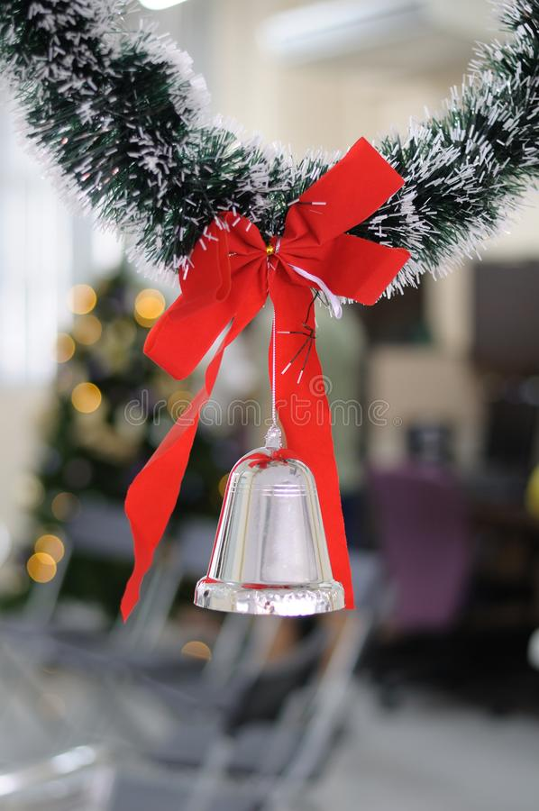 摇晃从一个绿色圣诞节花圈的红色丝带响铃的圣诞节装饰 免版税库存图片