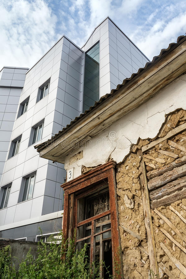 摇晃被毁坏的被放弃的老房子和现代新的大厦 库存图片