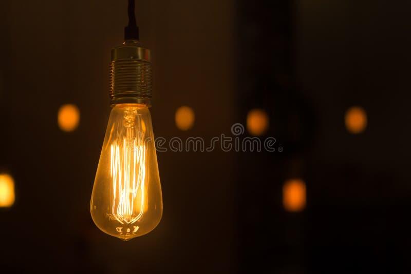 摇晃从天花板的发光的电灯泡 免版税库存图片