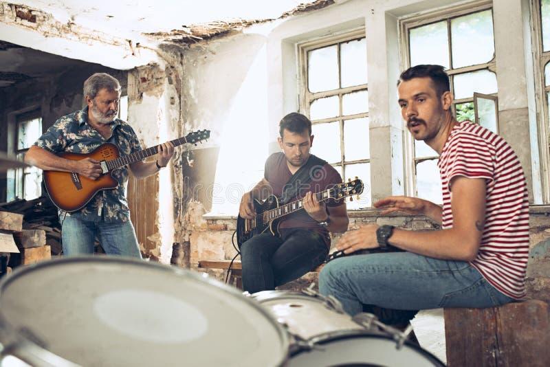 摇滚乐带的重复 电吉他球员和鼓手在鼓集合后 免版税图库摄影