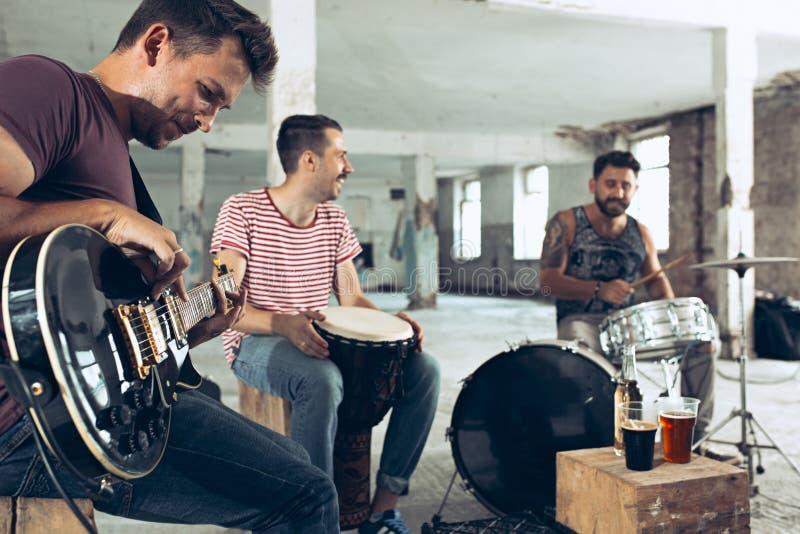 摇滚乐带的重复 电吉他球员和鼓手在鼓集合后 库存照片