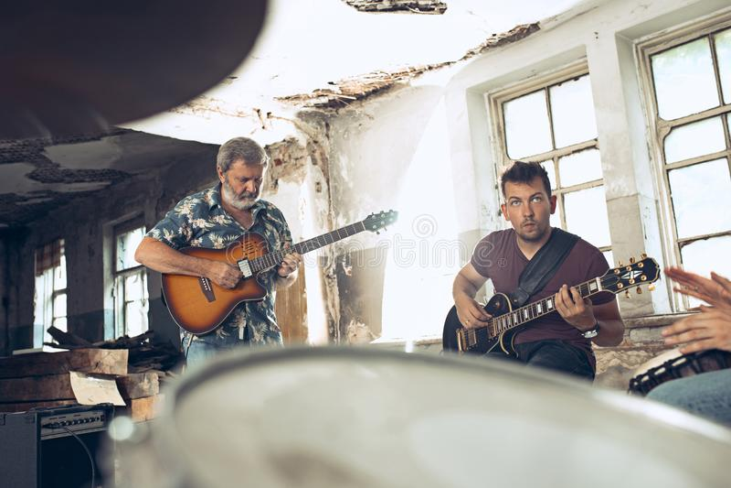 摇滚乐带的重复 电吉他球员和鼓手在鼓集合后 免版税库存照片