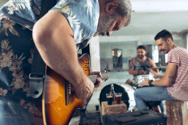摇滚乐带的重复 电吉他球员和鼓手在鼓集合后 免版税库存图片