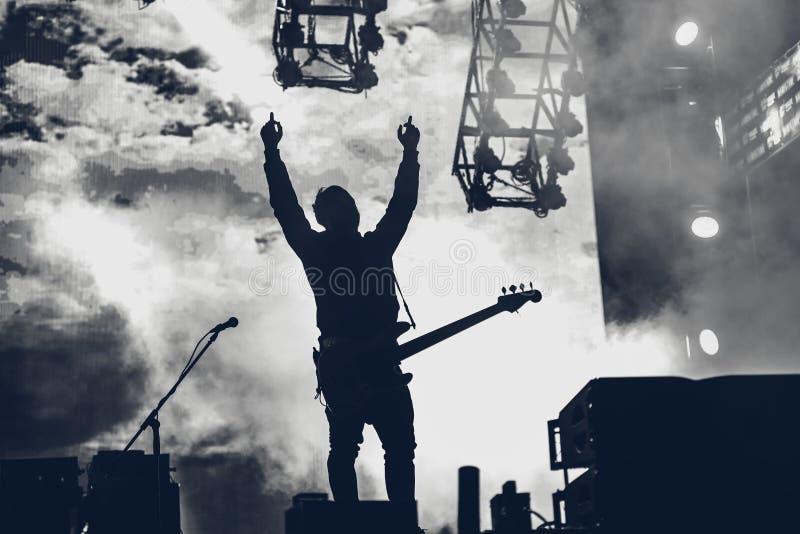 摇滚乐队在阶段执行 吉他弹奏者独奏使用 剪影  免版税库存图片