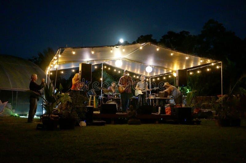 摇滚乐队Roxotica,以吉他弹奏者、低音歌手、使用在报道的发光阶段下的小提琴手和鼓手为特色 免版税库存照片