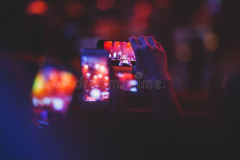 摇滚乐音乐会展示看法在大音乐厅,有人群和阶段光的,有场面的一个拥挤音乐厅点燃,岩石展示pe 图库摄影