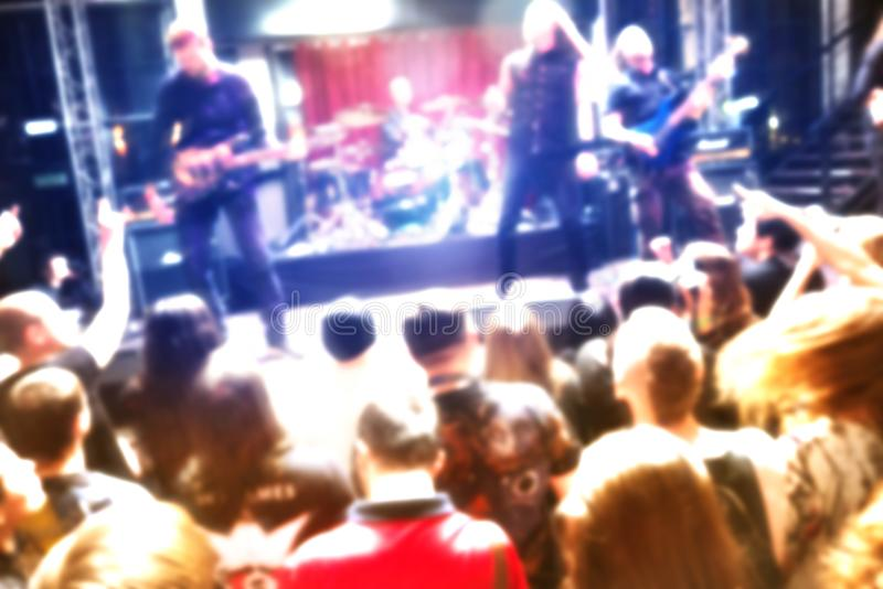 摇滚乐音乐会弄脏了从观众、岩石音乐家有吉他的和歌唱者的背景视图 库存图片