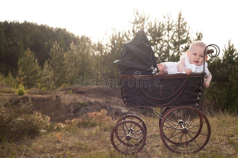 摇篮车的婴孩有日落的 免版税库存照片