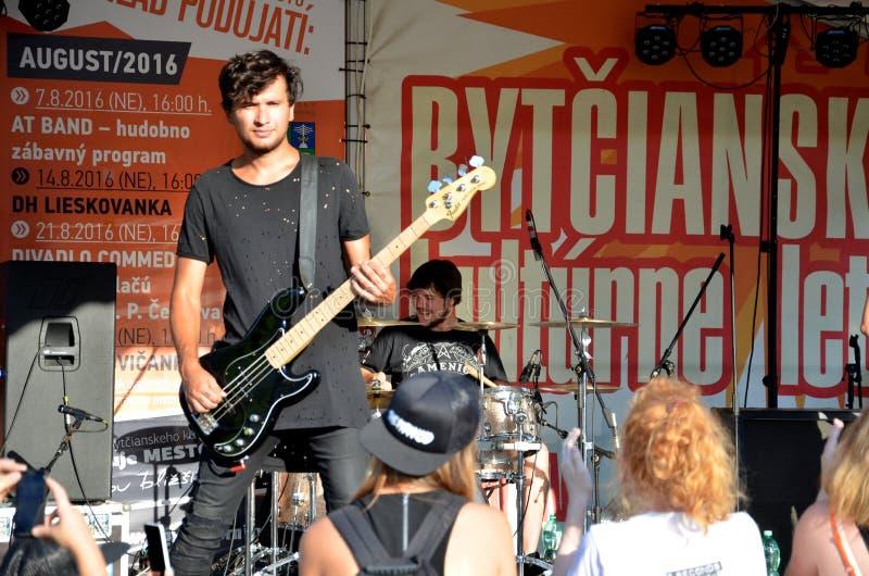 摇滚乐带露天音乐会告诉了偏执狂患者 在最前方的吉他弹奏者立场,鼓手使用  库存照片