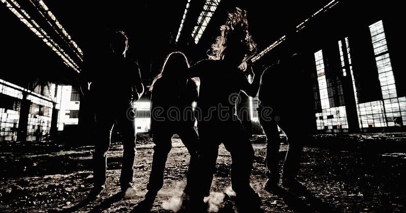 摇滚乐队小组照片在一个被放弃的工业大厅里 免版税库存图片