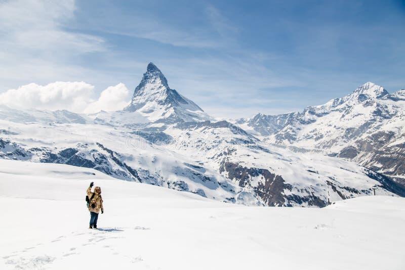 摇他的手的一个人站立在雪在马塔角背景中  库存图片