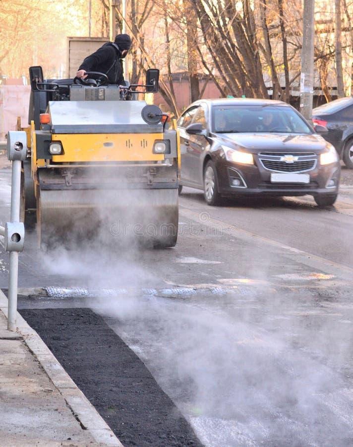 摊铺机的一名工作者在新鲜的沥青,沥青-滚动它的路修理驾驶 免版税库存照片