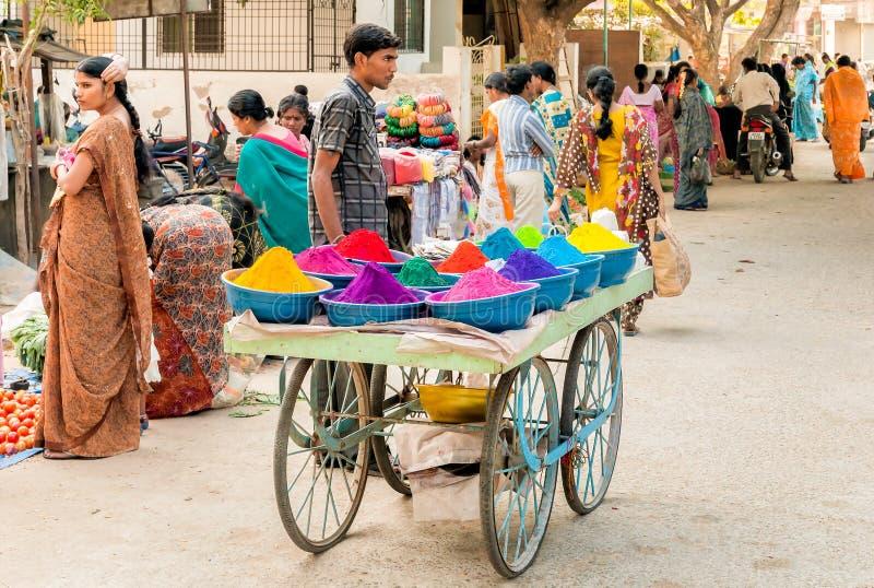 摊贩出售五颜六色的tika粉末在Puttaparthi,印度街市上  库存照片
