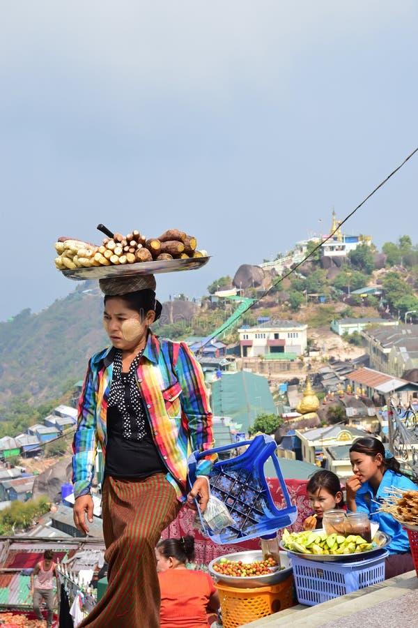 摊贩运载的盘子新近地煮熟的薯类,木薯和象在她的头 免版税图库摄影