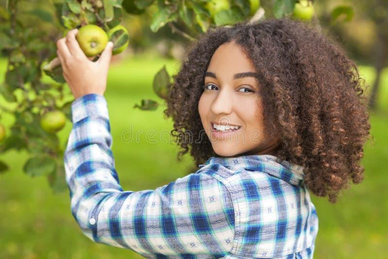 摘苹果计算机的混合的族种非裔美国人的女孩少年 库存照片