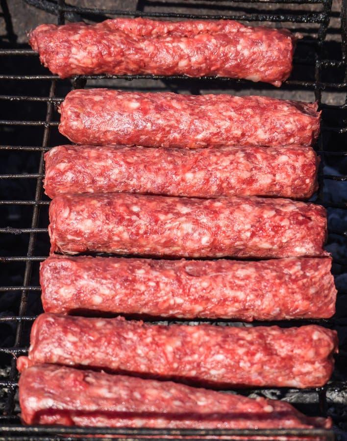 摩尔多瓦的mititei和烹调在烟的格栅 库存图片