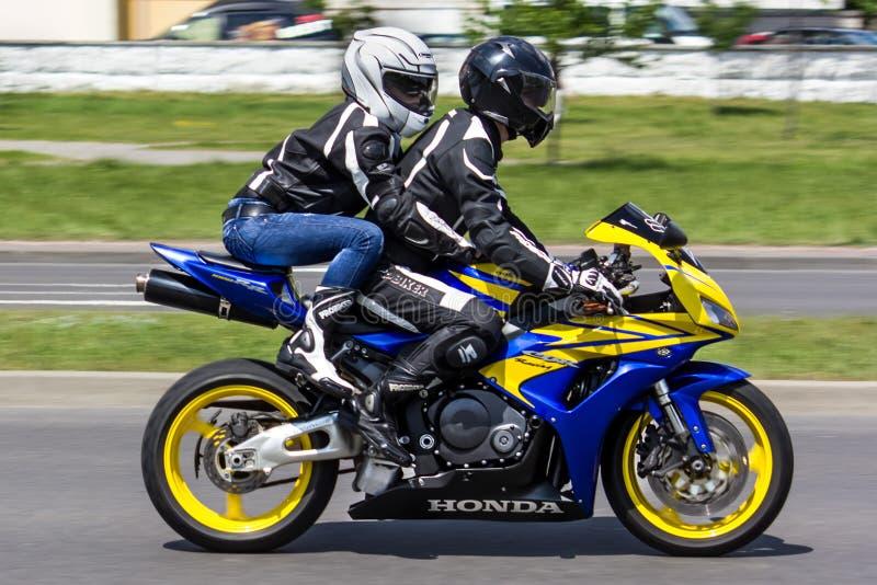 摩托车乘驾的两三个骑自行车的人通过布雷斯特的街道  库存照片
