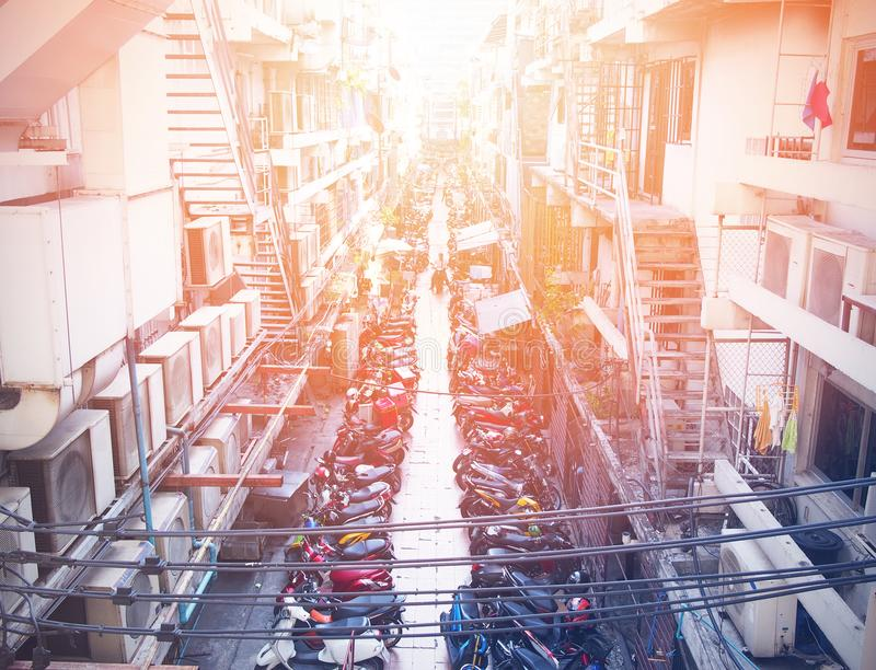 摩托车停车处在狭窄充塞了在大厦之间的路 免版税图库摄影