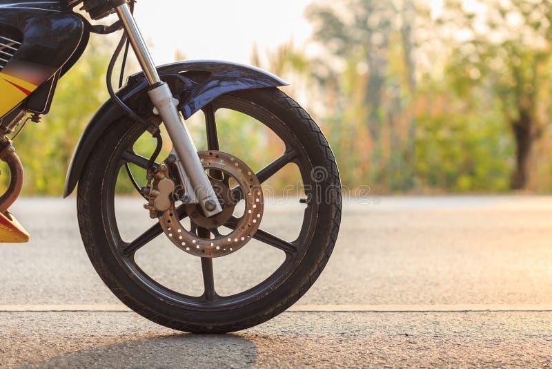 摩托车前轮在柏油路的 免版税库存图片