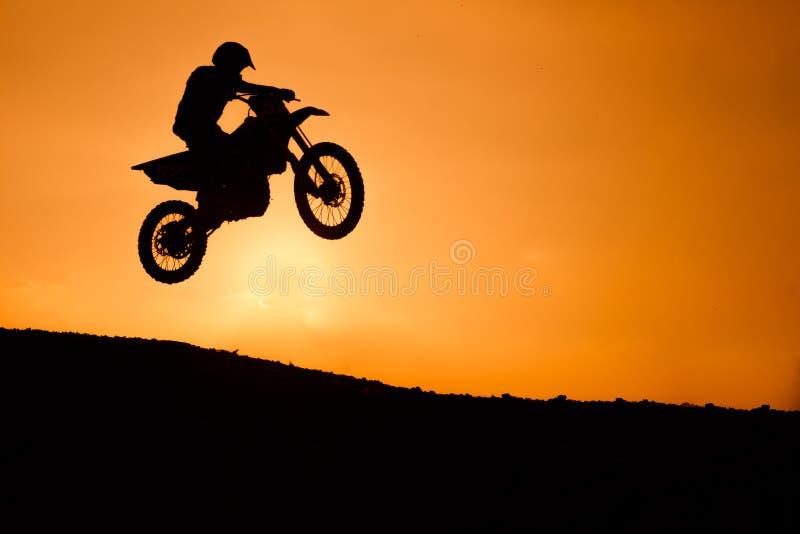 摩托车剪影跳跃 库存照片