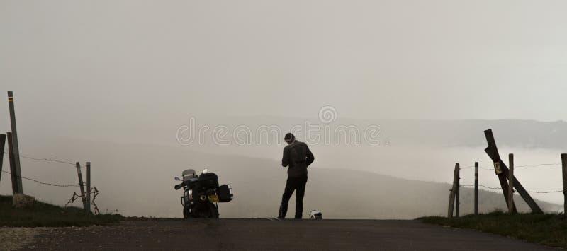 摩托车和常设车手现出轮廓反对一个有薄雾的谷 库存图片