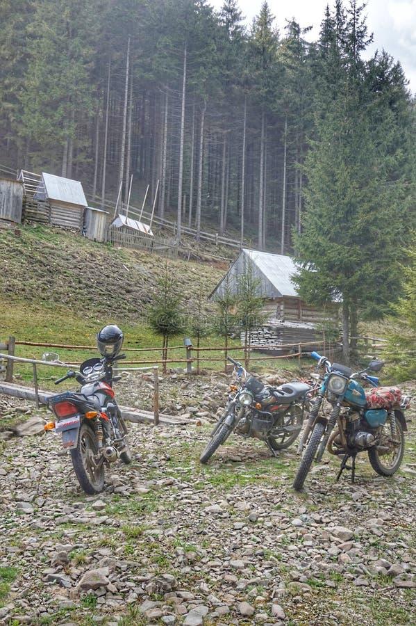 摩托车和滑行车在房子附近停放在山村 免版税库存照片